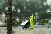 cop holding an umbrella for a disabled protester