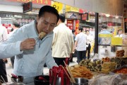 Former President Lee Myung-bak is eating food at a street stall.