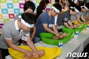 Fathers learn how to wash their babies at the 2013 Seoul International Baby Fair