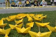 Families of the Sewol tragedy stage a hunger strike.  Yellow paper boats with messages to the victims are in the foreground.
